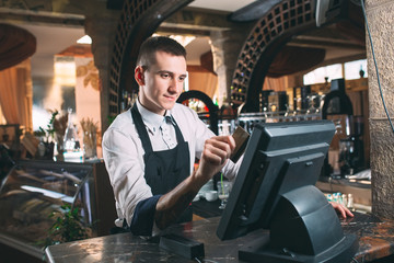 small business, people and service concept - happy man or waiter in apron at counter with cashbox working at bar or coffee shop Wall mural