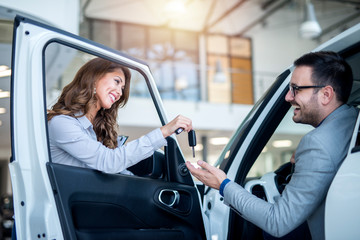 Professional car salesperson handing over keys to the customer of brand new vehicle at local car dealership.