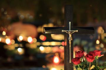 Piękny złoty wizerunek chrystusa na krzyżu na cmentarzu nocą w świetle palących się zniczy.