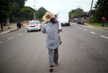 Stephen, a four-year-old migrant boy from Honduras, part of a caravan of thousands traveling from Central America en route to the United States, is carried by his father, Darwin as they walk along the highway to Sayula de Aleman from Donaji