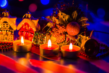 Merry Cristmas. Toy houses and candlelight. Christmas decorations on blurred background. Festive evening. Spruce branches and Christmas toys with bokeh. Copy space