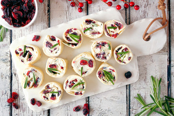 Spoed Fotobehang Voorgerecht Cranberry, cream cheese roll-up appetizers. Holiday food concept. Top view, on a white background.