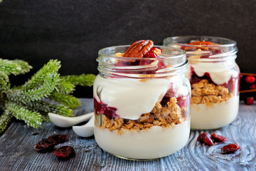 Cranberry granola parfaits in mason jars with a dark background