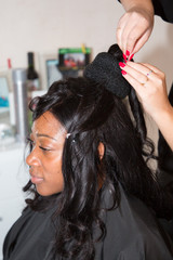 Professional hairdresser artist make wedding hairstyle to charming american black bride woman on wedding day