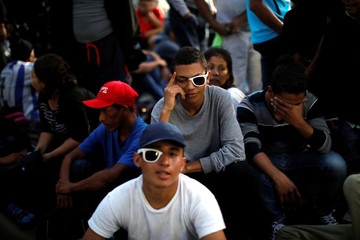 Migrants, part of a caravan travelling to the U.S., wait to cross the border between Guatemala and Mexico, in Tecun Uman