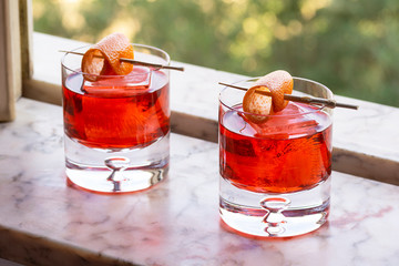 Two Red Negroni Cocktails Drinks on Ice with Orange Twist in Marble Windowsill
