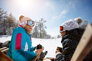 Two female talking with drink in sunbed on ski terrain