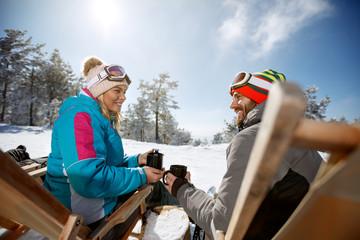 Woman and man on skiing in sunbed enjoy with drink
