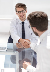 happy employees shake hands while sitting at the Desk.