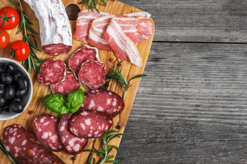 Food tray with delicious salami, bacon, smoked sausages, olives, tomatoes and herbs. Meat platter on rustic wooden table