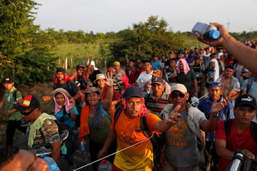 Migrants, part of a caravan traveling from Central America en route to the United States walk by the road that links Ciudad Hidalgo with Tapachula
