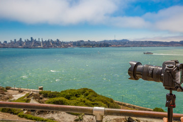 Sea view from Alcatraz island of camera taking pictures of the San Francisco Financial District skyline in California, United States.