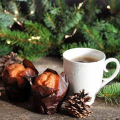 Christmas Breakfast of two cupcakes and a Cup of hot coffee on a wooden table, on the background of fir branches with lights.