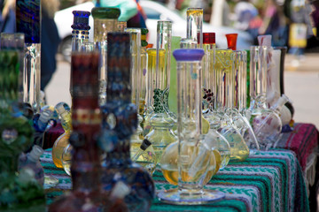 Close Up, Isolated View of Glass Bongs on Flea Market Table, Sunlit Out of Focus Background