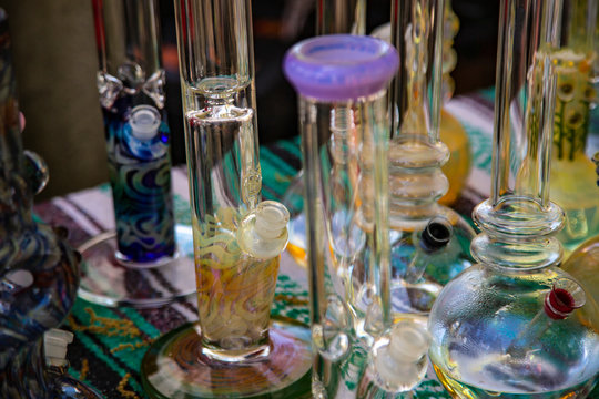 Isolated Close Up View of Glass Bongs on Flea Market Table, Sunlit Out of Focus Background