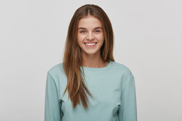 Portrait of a beautiful cheerful happy young girl with natural make-up and well-groomed hair, smiles, wears casual blue long sleeve t-shirt, on a white background in the studio.