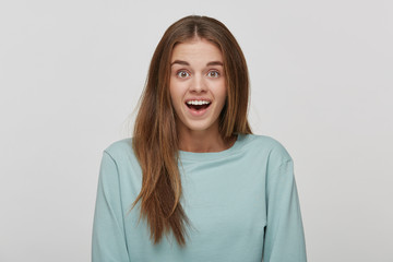 Surprised joyful beautiful female with amazed expression, looks with bugged eyes and keeps mouth open, dressed casual blue long sleeve t-shirt, over white background. Human reaction and emotions