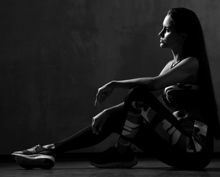 Young sport woman in workout exercise cloth posing sitting stretching in gym on dark grey