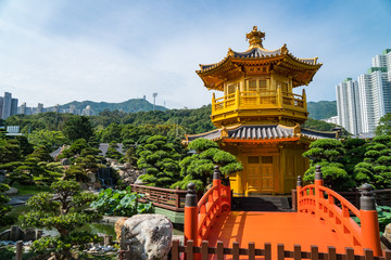 Beautiful golden pagoda in a peaceful garden surrounded by trees with a blue sky in the city