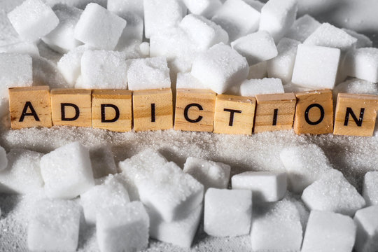 pile of sugar cubes and addiction word in block letters as advise on calories excess and sweet unhealthy food abuse causing health problem and overweight