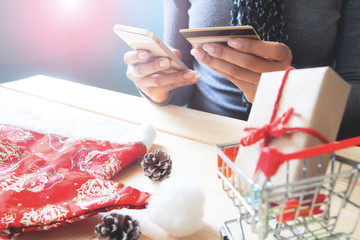 Woman using mobile phone and credit card. Christmas shopping online