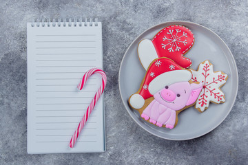 Christmas Ginger Cookies Cute Pig Symbol Year and empty paper notebook on a gray stone concrete table background. Top view with copy space, flat lay