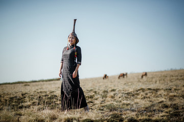 Tuvan girl in national dress in the steppe with horses