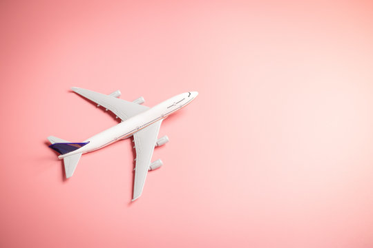 Model plane, top view of airplane on pink color background. travel planning concept