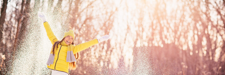 Happy winter girl playing outside throwing snow outdoor in forest having fun - banner panorama lifestyle.