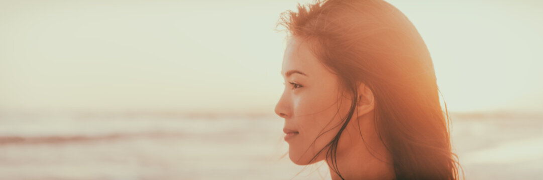 Asian woman beauty portrait serene on beach at sunset looking at ocean pensive -Panorama banner face of chinese girl happy.