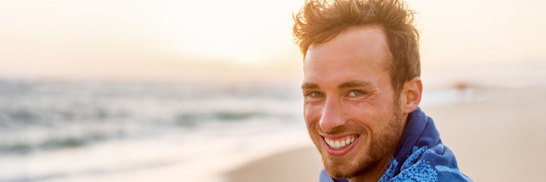 Smiling handsome young man beauty portrait on beach at sunset looking at camera laughing, healthy grin -Panorama banner face of happy model in towel.