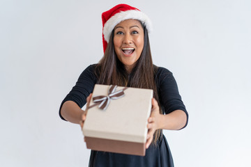 Jolly Christmas lady giving gift. Excited woman in Santa hat offering present box at camera. Christmas gift or prize concept