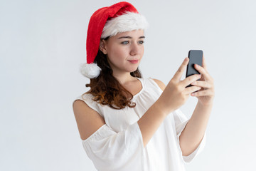 Positive girl in Santa hat having video call, testing camera or mobile app. Pretty young woman using smartphone. Connection concept