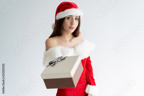 e505616fe63e7 Pensive cute Christmas girl giving gift. Beautiful young woman in Santa hat  offering present box. Christmas gifts delivery concept