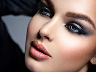 Closeup face of a beautiful girl with  makeup in style smoky eyes.