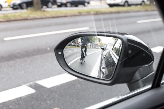 Cyclist in the exterior mirror of a car