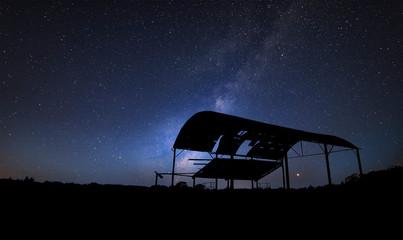 Vibrant Milky Way composite image over landscape of old derelict barn