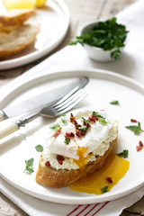 Crispy baguette toasts with cottage cheese, poached egg and dried tomatoes on a light background.