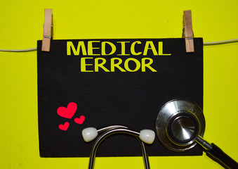 A stethoscope and blackboard with word MEDICAL ERROR on top of yellow background. Medical, health and education concepts