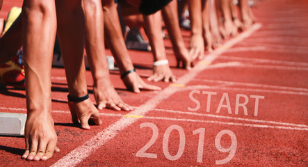 2019 the start into the new year.sports background.hand of runner feet running on racetrack