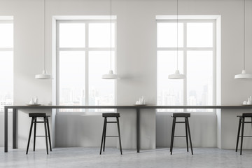 White cafe interior, black stools