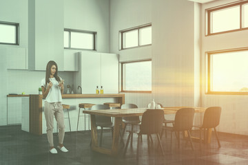 Woman in white kitchen and dining room