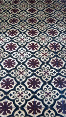 Brown and white floor tiles with floral design