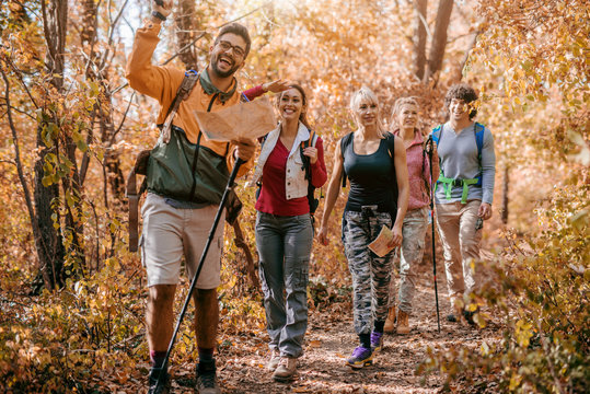 Man holding map and showing other hikers right way while walking in woods.