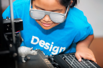 A smart young girl of mixed race, wearing a shirt that says design, is overlooking the 3d printout of a gray rhinoceros for her STEM class.