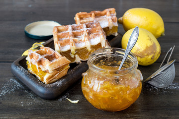 Sweet dessert. A small glass jar of fruit jam, a homemade waffles and fresh yellow lemons on an old wooden table.