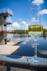 Close-up on a glass of sparkling champagne mirroring the diving platform, blue sky and clouds and the lake in the background