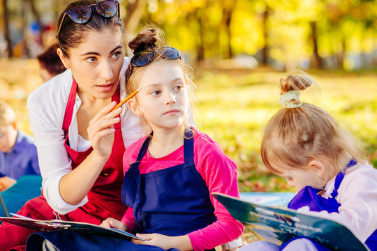Female teacher explaining for two little sisters school girls how working with a brushes and paints in fall park. Creative child painting on nature sitting on ground. Activity for children concept.