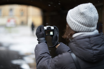 girl in gloves in the fall photographs mirrorless camera. view from over the shoulder, the camera in hand. the first falling snow.