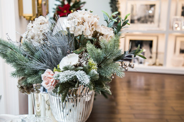 Decorated vase with beautiful white flowers and christmas tree branches, bright interior with decorations on the background